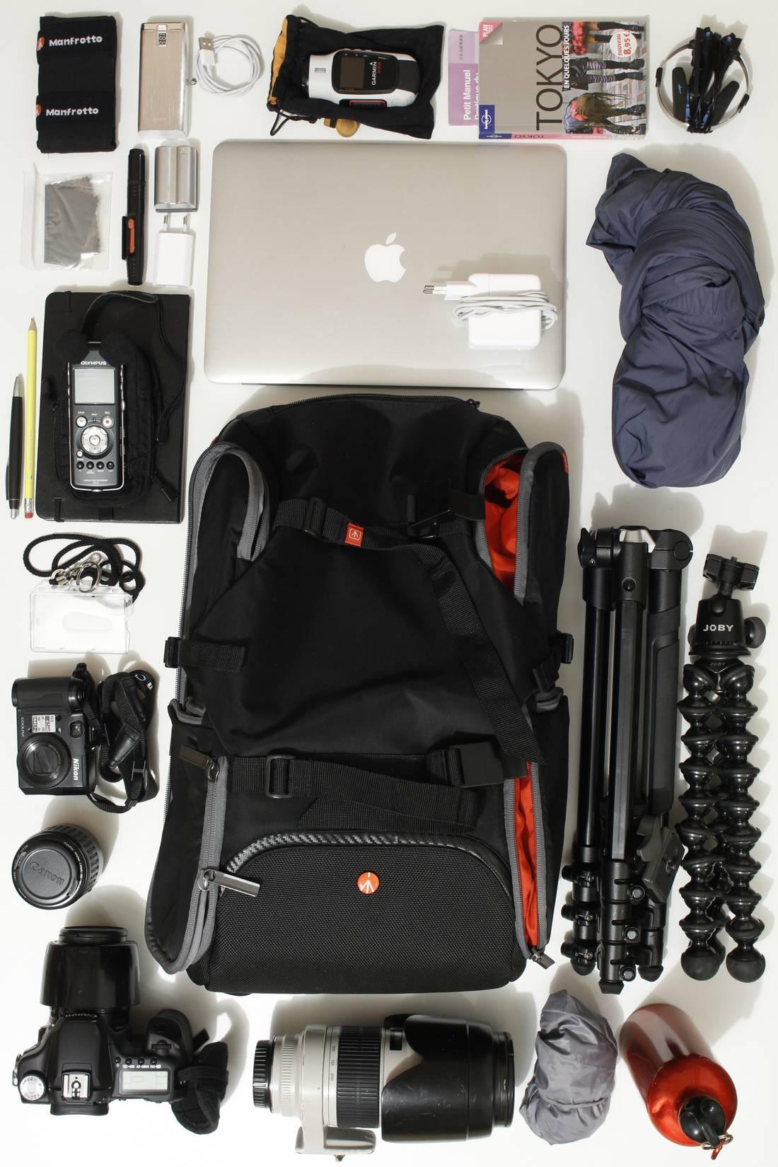 Le sac à dos photo Manfrotto Travel Backpack, entouré du matériel et de divers objets qu'il peut contenir. Ph. Moctar KANE.